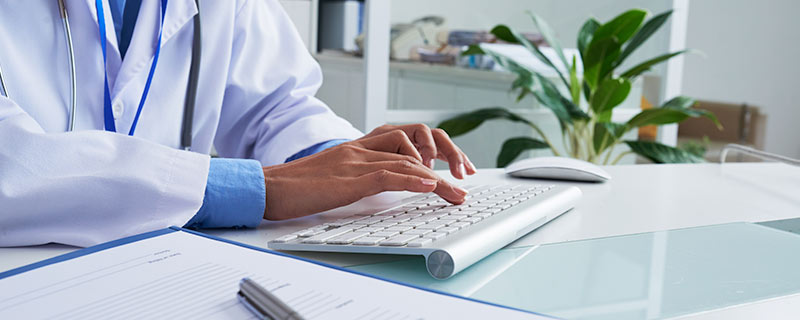 Photo of doctor typing on keyboard